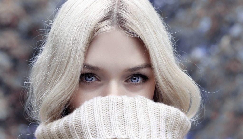 blonďatá dívka ve svetru schovává rty