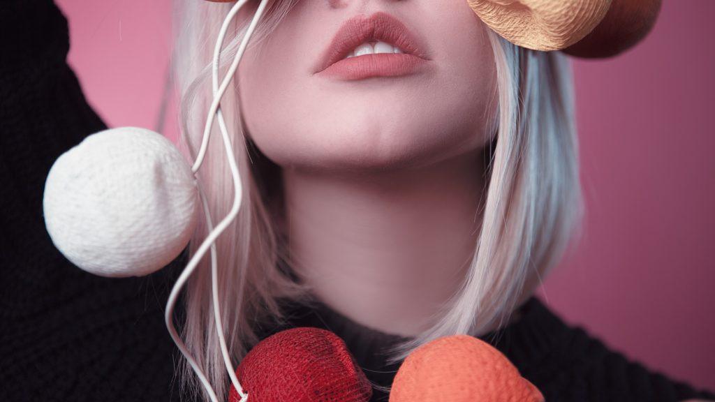 dívka s růžovými rty a svítícími balonky